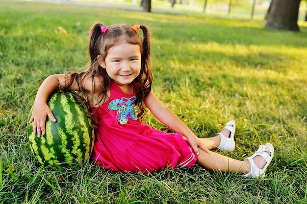 草の上の公園で巨大なスイカにもたれて子供面白い小さなアジアの女の子