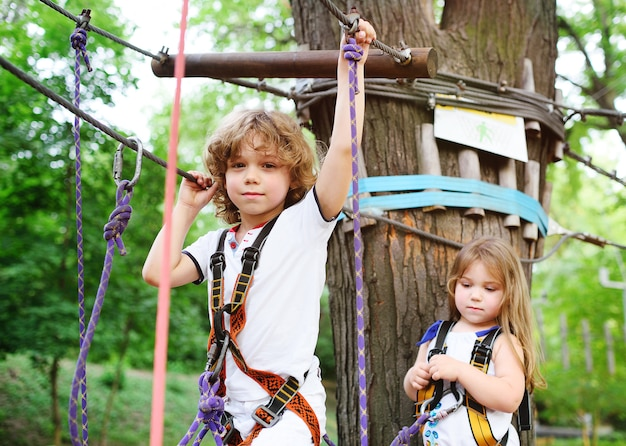 Дети - мальчик и девочка в канатном парке проезжают препятствия