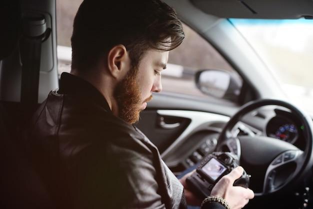 車の中でカメラを持つ若い男