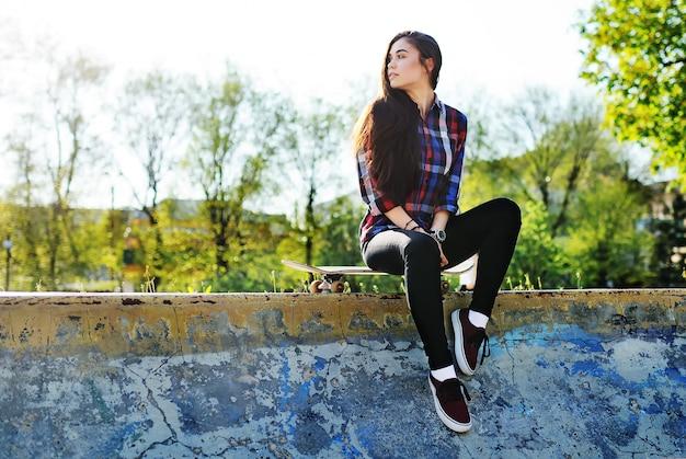 Симпатичная девушка со скейтбордом на фоне парка