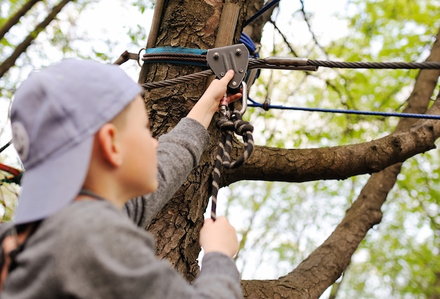 未就学児の男の子が安全アルピニズム装備ハイロープコースで障害となっている