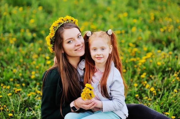 赤い髪の少女は、タンポポのフィールドの背景に彼女のお母さんを抱擁します。