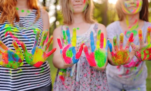 若い女の子のグループは、着色された指の塗料で汚れた手のひらを示しています