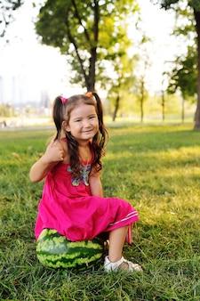 Ребенок смешная маленькая азиатская девушка, опираясь на огромный арбуз в парке на траве в летний день
