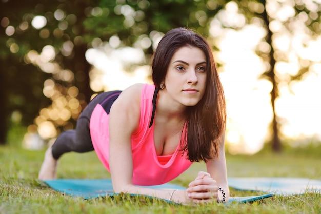 屋外公園の緑の芝生に板運動をしている若い美しい運動女性