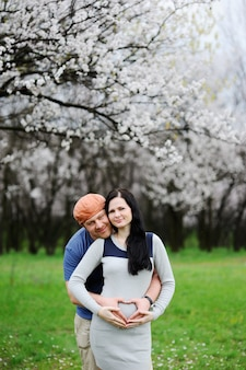Мальчик и девочка на цветущий абрикос. парень обнимает беременную женщину