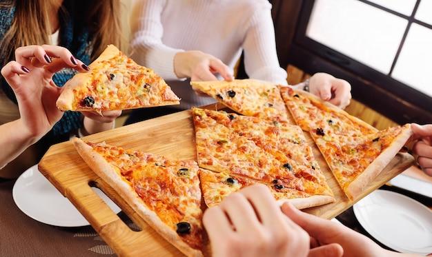 友人のグループがカフェに座って新鮮な熱いピザをつかみます