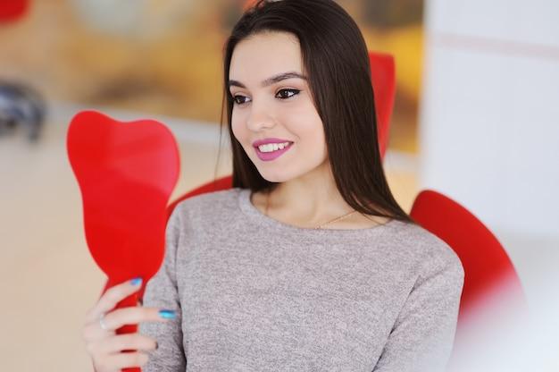 赤い歯科用椅子に笑っている美しい若い女の子