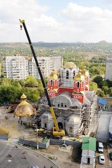 クレーンは正教会の黄金のドームを持ち上げます。教会の建設と再建
