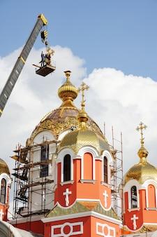 ビルダーは教会の建設中の黄金の正統派正教会の十字架に乗った。