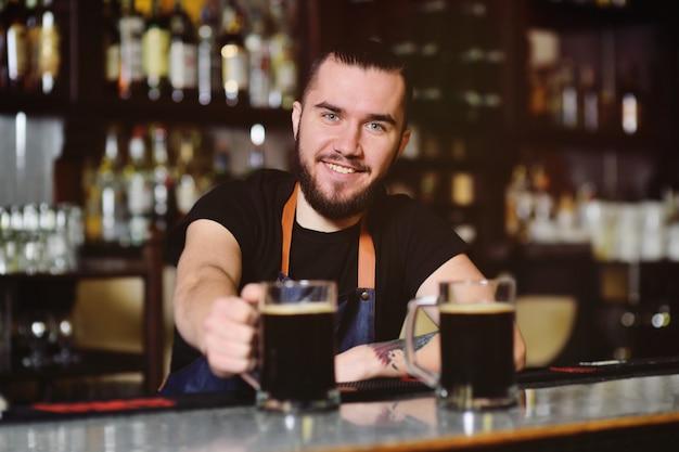 バーで笑顔のビールのジョッキで若いかわいいバーテンダーの背景。オクトーバーフェスト