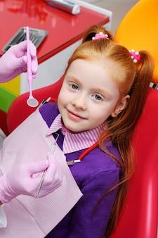 Маленькая девочка, улыбаясь в красный стоматологическое кресло. стоматолог осматривает зубы пациента ребенка.