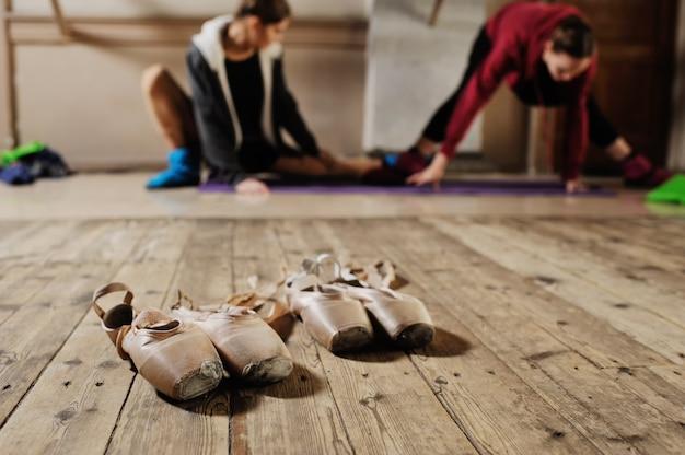 バレエのクラスでトレーニングする前にウォーミングアップしてストレッチする若いダンサーを背景にしたバレエのポアントのクローズアップ
