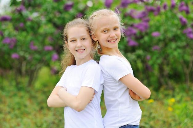 小さな子供のガールフレンドは笑みを浮かべて、公園の緑。
