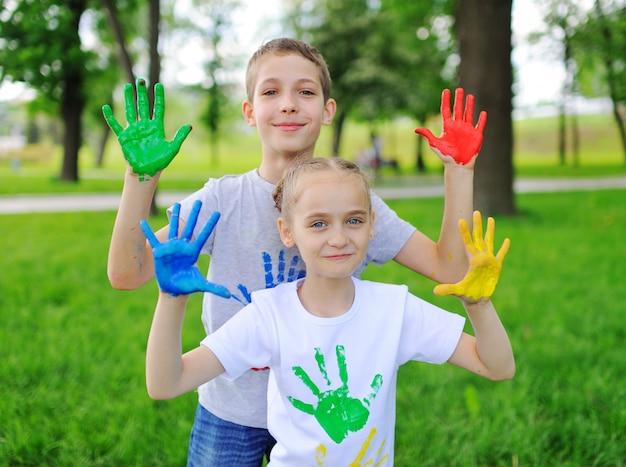 子供は公園で笑っている明るい色の指絵の具で塗られています。