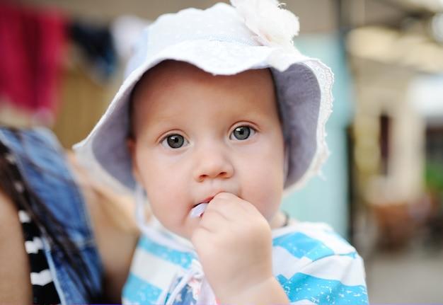 母の手で女の赤ちゃんは彼女の指を吸う