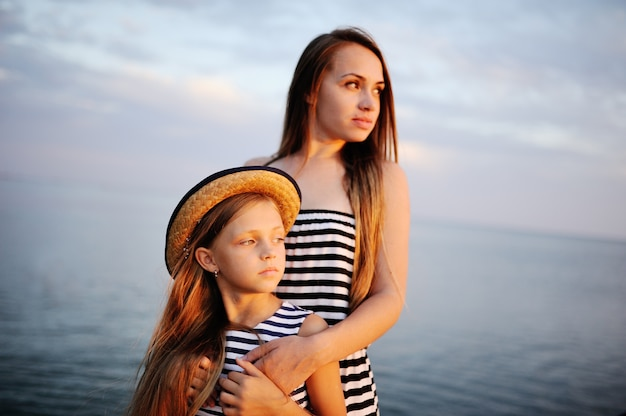 背景の夕日の海に縞模様の布で二人の女の子