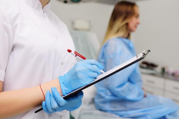 Врач гинеколог осматривает беременную женщину с большим животом на фоне современной клиники