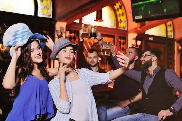 Юноши и девушки в баварских шапках пьют пиво