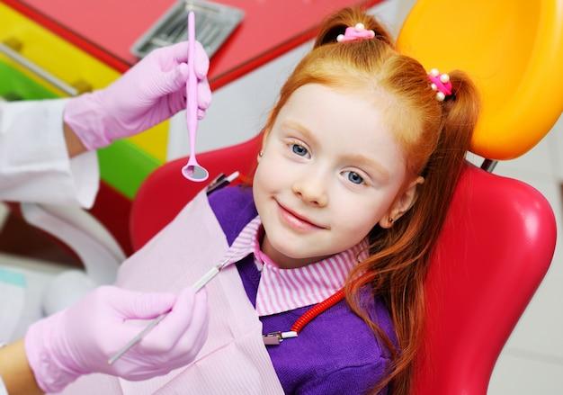 赤い歯科用椅子に笑みを浮かべて少女。