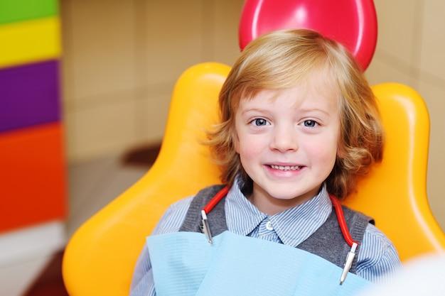 歯科用椅子で金髪の巻き毛の男の子の笑みを浮かべてください。