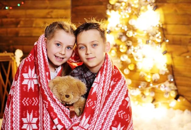Маленькие дети - мальчик и девочка, покрытые теплым красным одеялом в скандинавском стиле с игрушечным медведем в руках
