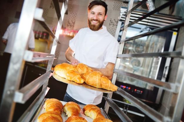 Красивый пекарь в белой форме держит в руках поднос, полный свежеиспеченных круассанов против пекарни