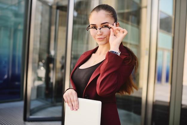事務所ビルの背景に手でコンピューターのタブレットとメガネのビジネスの少女