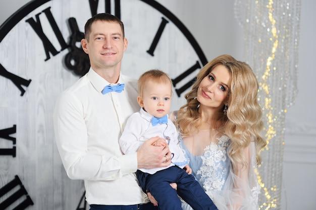 若い家族のお母さん、お父さん、上品な服を着た幼い息子がクリスマスを祝う