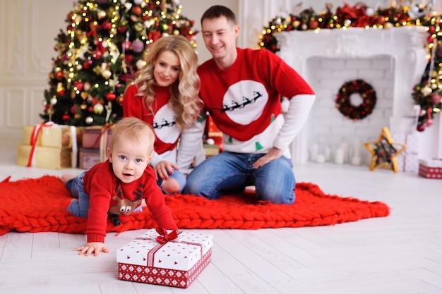 鹿と赤いクリスマスセーターの小さな男の子は、クリスマスプレゼントをクロールします。