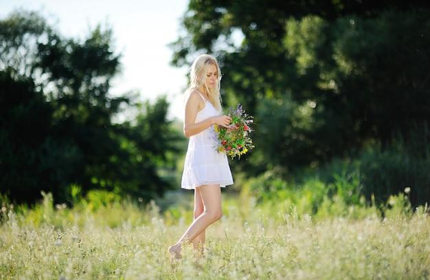 白いサンドレスと手に花の花輪を持つ少女