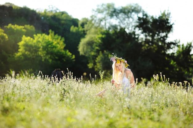 白いサンドレスと草の中に座っている彼女の頭の上の花の花輪の女の子