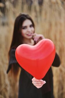 Красивая молодая женщина с воздушным шаром в форме сердца