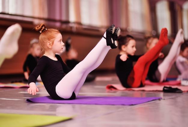 Маленькая милая рыжеволосая балерина выполняет упражнения на растяжку в балетной школе