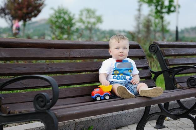 おもちゃの車を手に、ベンチに座っている男の子