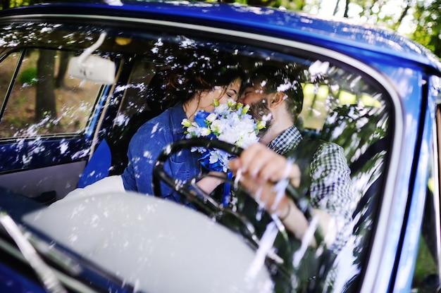 少年と少女は青いレトロな車の近くを抱いて。