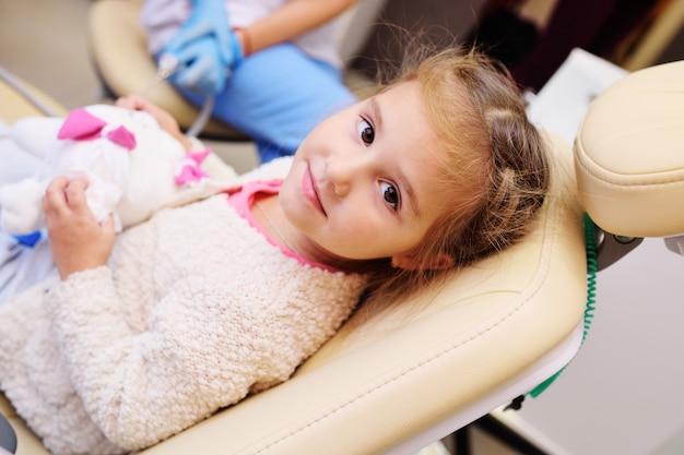 Девочка сидит в стоматологическом кресле держит мягкую игрушку в виде зуба.