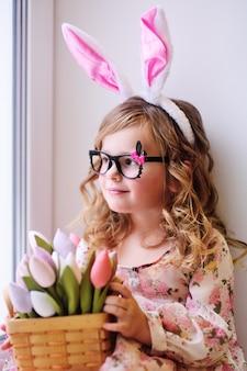 Красивая маленькая девочка в нарядном платье сидит на подоконнике с букетом цветов тюльпанов на поверхности окна.