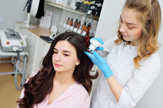 皮膚科専門医は、若い女性にとって魅力的な患者の髪の状態のコンピューター診断を行います