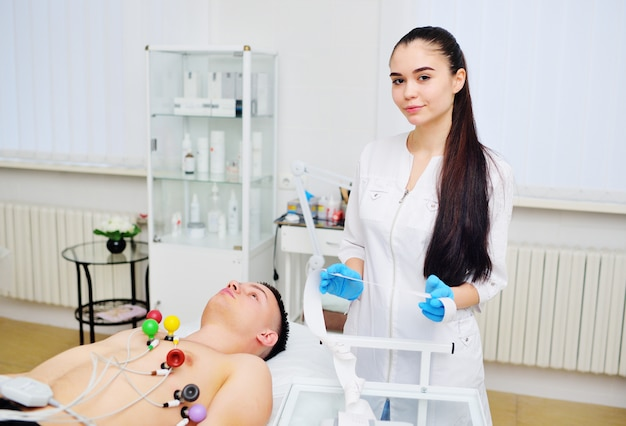 Доктор кардиолога молодой женщины держа бумажную кардиограмму против поверхности пациента мужского пола с вакуумными кардиодатчиками для экг или электрокардиограммы. профилактика сердечно-сосудистых заболеваний.