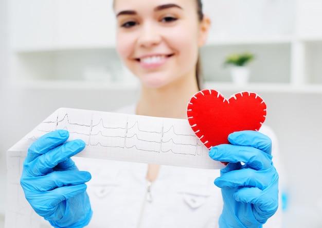 Женщина-врач держит красное сердце и бумажную распечатку кардиограммы. профилактика сердечно-сосудистых заболеваний.