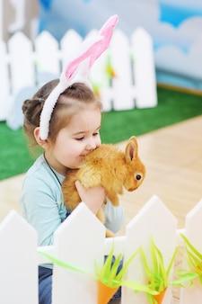 Девочка с ушами кролика держит маленький красный пушистый кролик. пасхальная концепция