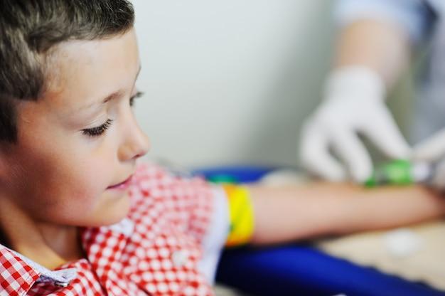 医師または看護師は、男の子の子供の静脈から血液を採取します。血液化学