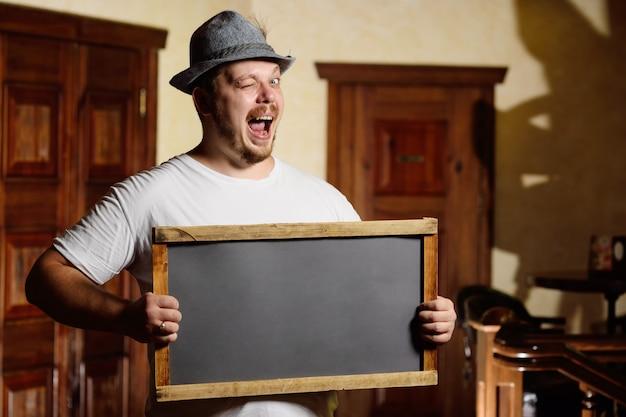 Толстый веселый человек в баварской шляпе с пером во время празднования октоберфеста держит в руках табличку или доску