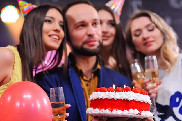 イベントを祝うためにお祝い帽子で陽気な友人の会社