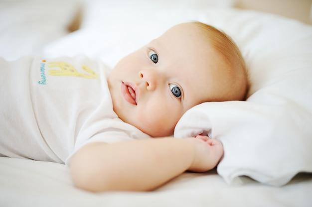 青い目を持つ赤ちゃんの肖像画。ベッドで休む子供