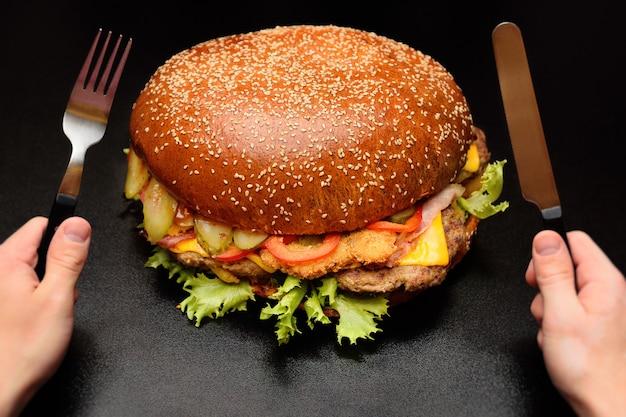 Огромный гигантский большой бургер на темной поверхности крупным планом