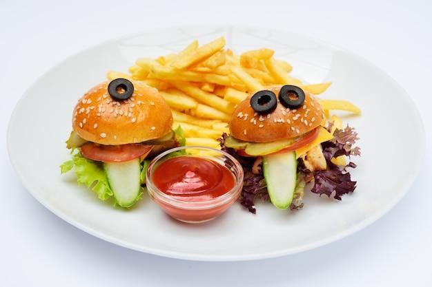 Смешные детские бургеры на тарелке крупным планом с картофелем фри и соусом