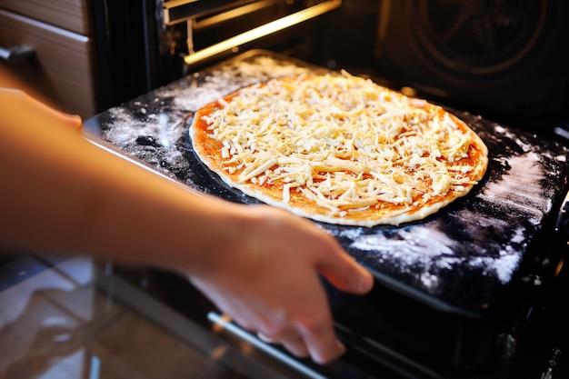 ピザを調理します。女性の手は、ピザのクローズアップのオーブンの形に置きます。手作りケーキ