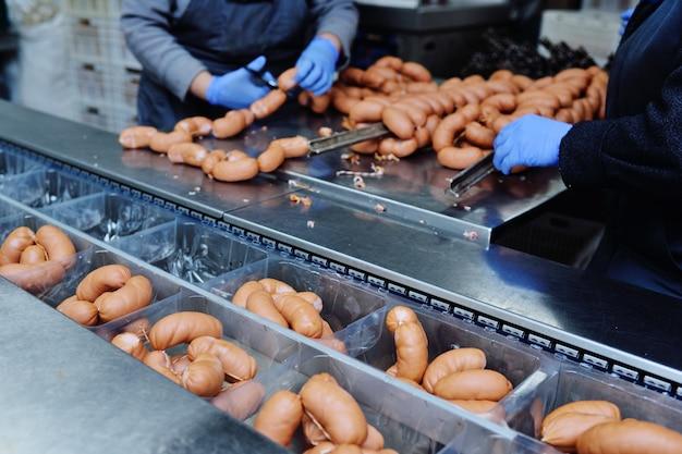 Сосиски, висящие в коптильне крупным планом на мясокомбинате